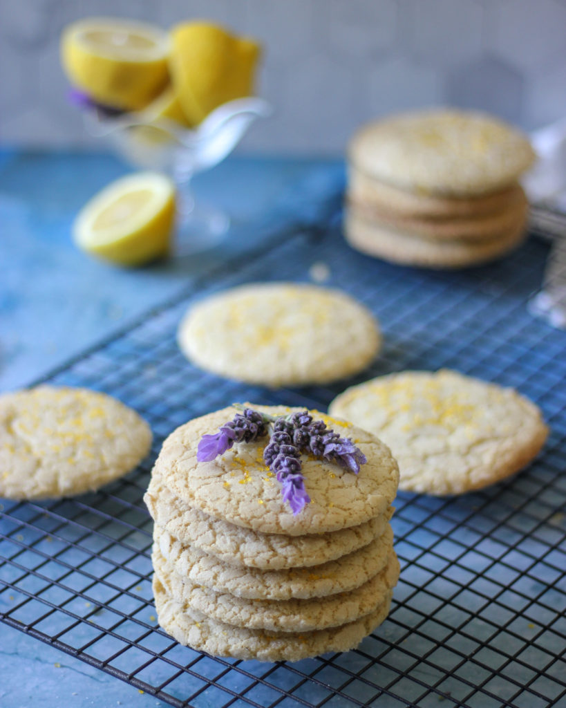 Lemon Lavender Snickerdoodle Cookies on a rack, topped with fresh lavender flowers